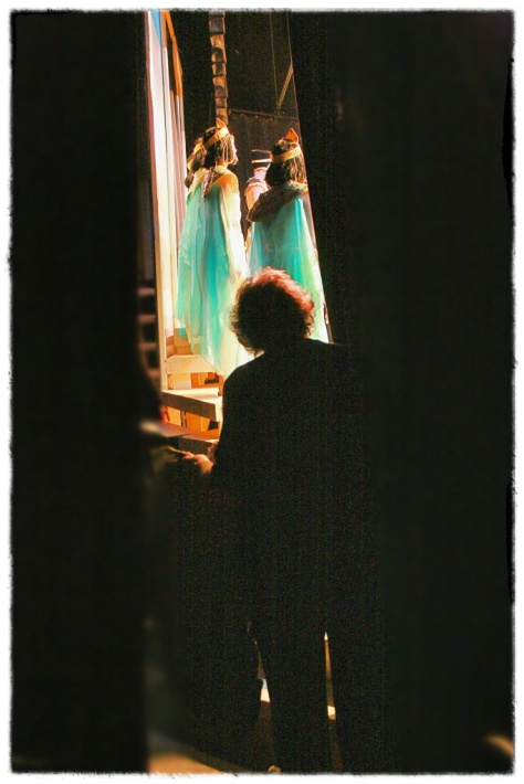 Costumer Pati Van Zante stands backstage waiting to hand props to the actors on stage.