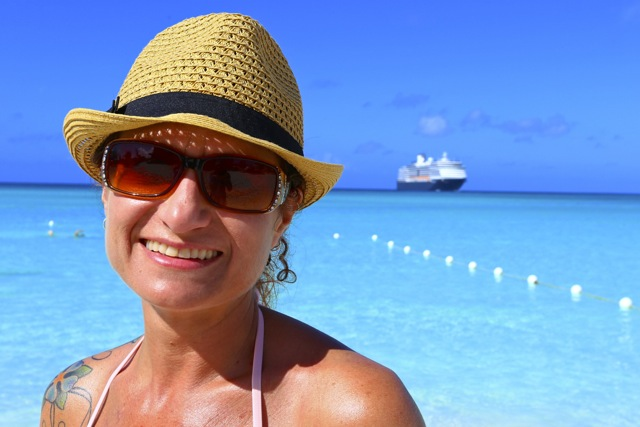 Wendy on the beach of Half Moon Cay, Bahamas. Our ship is in the distance.