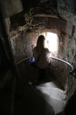 Taylor looks out the window from the steep winding tower stair of Doune Castle.