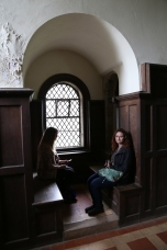 Taylor and Wendy sitting in a restored side bench in the Royal hall of Doune Castle.