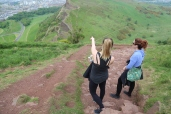 Taylor pointing out Edinburgh landmarks while climbing Arthur's Seat.