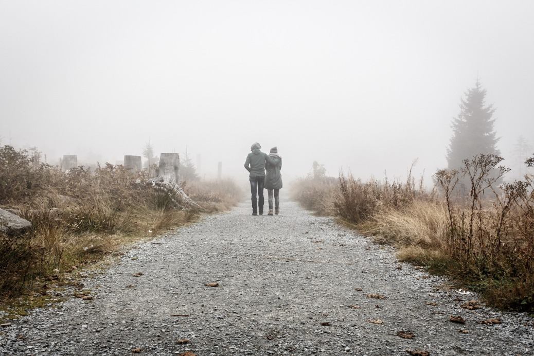 Gray Couple walking on misty road